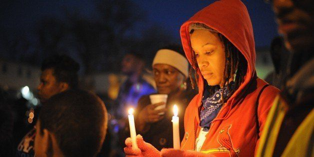 A woman holds a candle while protesters demonstrate against racism in the 'Reclaim MLK' march January 19, 2015 in Canfield Ap