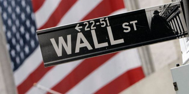 The flags on the facade of the New York Stock Exchange are a backdrop for a Wall Street street sign, Thursday morning, Aug. 1