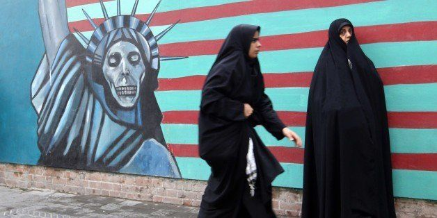 Iranian women walk past the painted wall of the former US embassy on November 4, 2014 in Tehran where takes place a demonstra