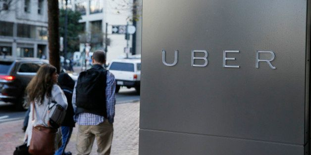 In this photo taken Tuesday, Dec. 16, 2014, a couple walks past the headquarters of Uber in San Francisco. (AP Photo/Eric Ris