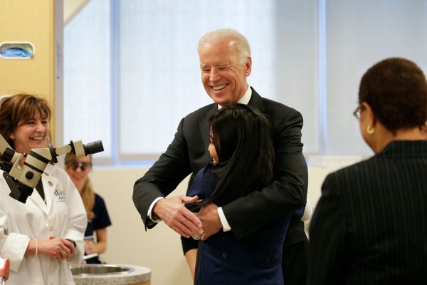Vice President Joe Biden hugs student Norina Del Rosario while touring a dental hygiene lab at West Los Angeles College on Fr
