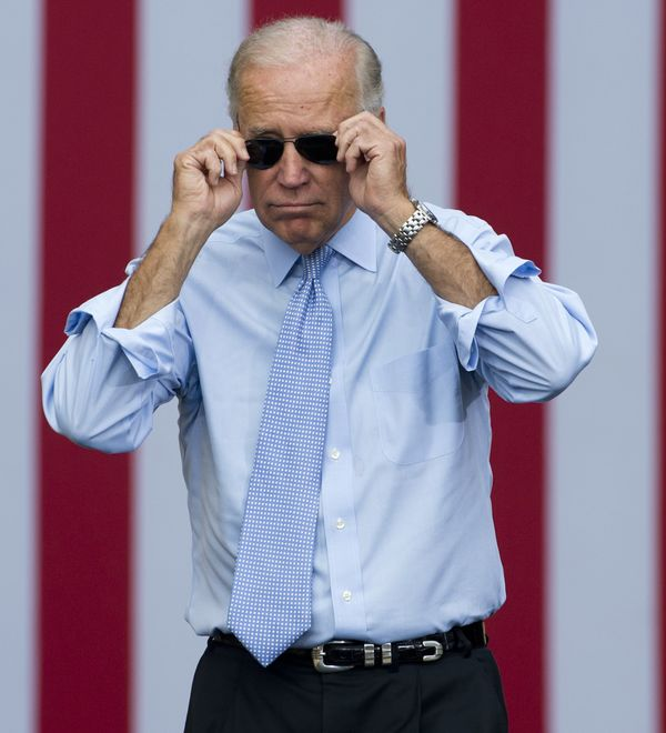 Vice President Joe Biden takes his sunglasses off as he arrives for a campaign event with President Barack Obama at Strawbery