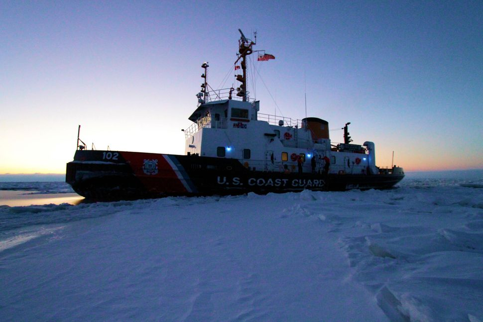 The crew of the Coast Guard Cutter Bristol Bay witnesses the morning sunrise while sitting in a frozen section of Lake Huron,