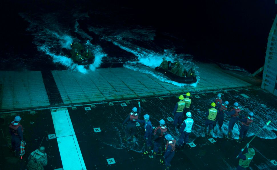 Sailors recover combat rubber raiding craft with Marines assigned to the 31st Marine Expeditionary Unit (31st MEU) during nig
