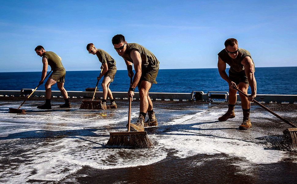 Marines with Marine Medium Tiltrotor Squadron 163 (Reinforced), 11th Marine Expeditionary Unit, scrub the flight deck of the
