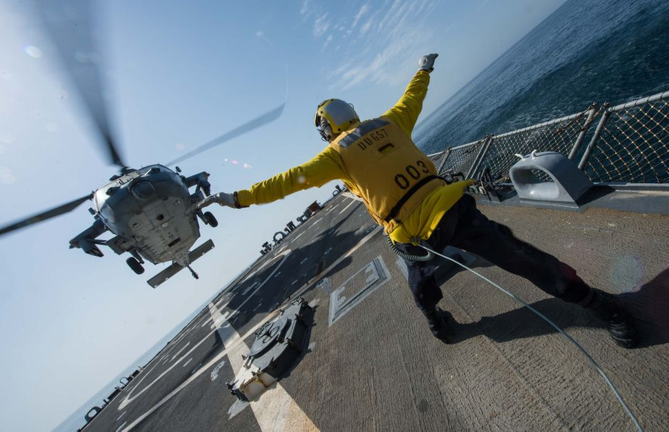 Boatswain's Mate 2nd Class John Acheson signals an MH-60S Sea Hawk helicopter from the Desert Hawks of Helicopter Sea Combat