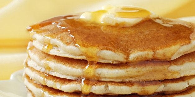 Golden pancakes with butter and warm maple syrup. Close-up with extremely shallow dof and soft yellow background.