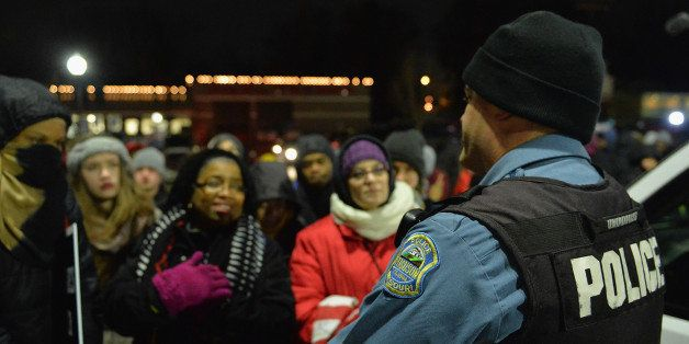 FERGUSON, MO -  MARCH 4: A Ferguson police officer listens to the concerns of a protestor as they demonstrate outside the Fer