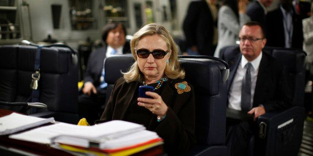 FILE - In this Oct. 18, 2011, file photo, then-Secretary of State Hillary Rodham Clinton checks her Blackberry from a desk in