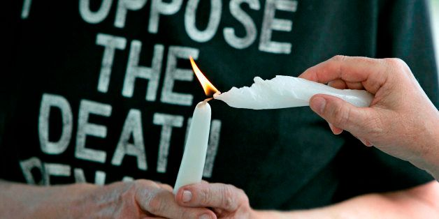 Anti-death penalty advocates light each other's candles during a prayer service for the souls of death row inmate Dale Leo Bi