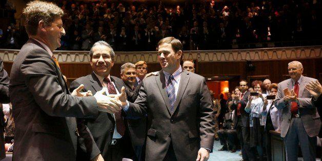Arizona Gov. Doug Ducey, middle, shakes hands with Phoenix Mayor Greg Stanton, left, as Roberto Rodriguez Hernandez, second f