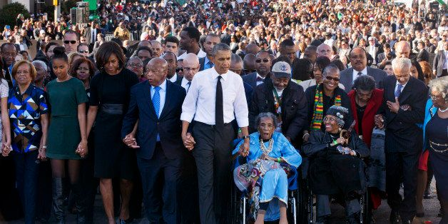 "President Barack Obama, center, walks as he holds hands with Amelia Boynton Robinson, who was beaten during ""Bloody Sunday,"""