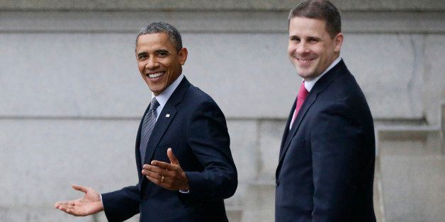 President Barack Obama, accompanied by White House Communications Director Dan Pfeiffer, reacts to a reporter's question abou