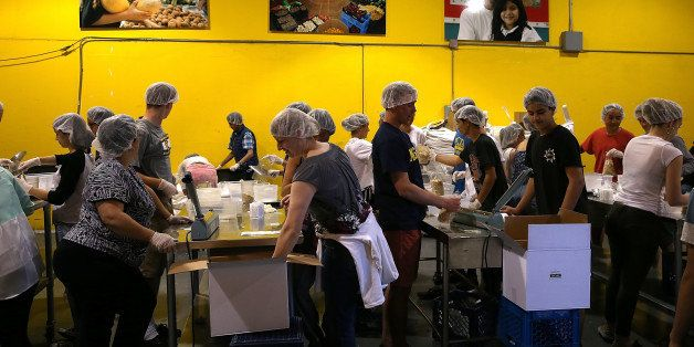 SAN FRANCISCO, CA - MAY 01: Volunteers pack bags of oatmeal at the SF-Marin Food Bank on May 1, 2014 in San Francisco, Califo