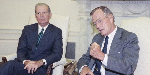 U.S. President George H. Bush drives home his point while he and Secretary of State James A. Baker III talks with reporters d