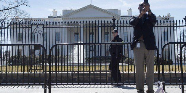 An uniformed US Secret Service officer (C) patrols Pennsylvania Avenue in front of the White House in Washington, DC, March 1