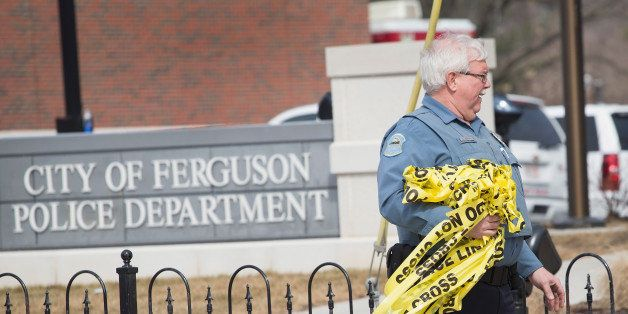 FERGUSON, MO - MARCH 12:  A police officer removes crime scene tape from outside the police station following an investigatio