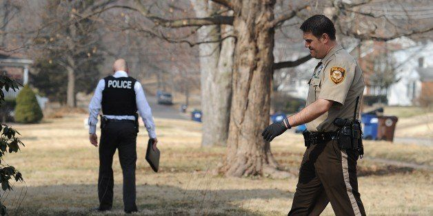 Police officials conduct an investigation in the Ferguson, Missouri neighborhood near the area of the overnight shooting of t