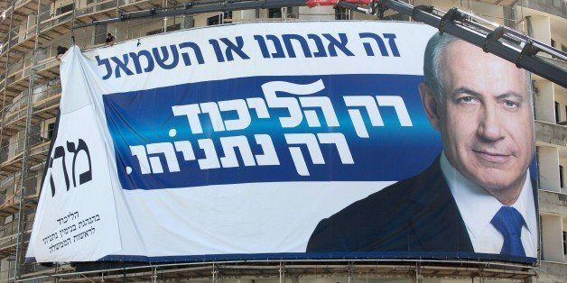 Workers hang on a building a giant campaign poster showing Israeli Prime Minister and Likud party's candidate running for gen