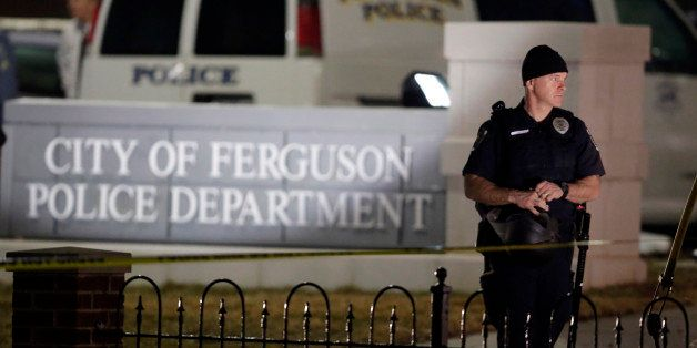 Police stand watch outside the Ferguson Police Department where two police officers were shot Thursday, March 12, 2015, in Fe