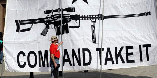 "A demonstrator helps hold a large ""Come and Take It"" banner at a rally in support of open carry gun laws at the Capitol, Mond"