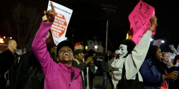 People demonstrate across the street from the Ferguson Police Department, Thursday, March 12, 2015, in Ferguson, Mo. Two poli