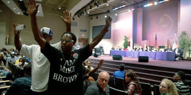 FILE - In this Sept. 9, 2014 file photo,  Marurice Brown raises his arms during a public comments portion of a meeting of the