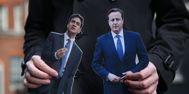 LONDON, ENGLAND - MARCH 18:  A TV reporter holds cut out photographs of Prime Minister David Cameron and opposition Labour Pa