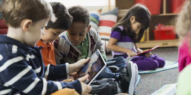 Boys using digital tablet together in elementary school