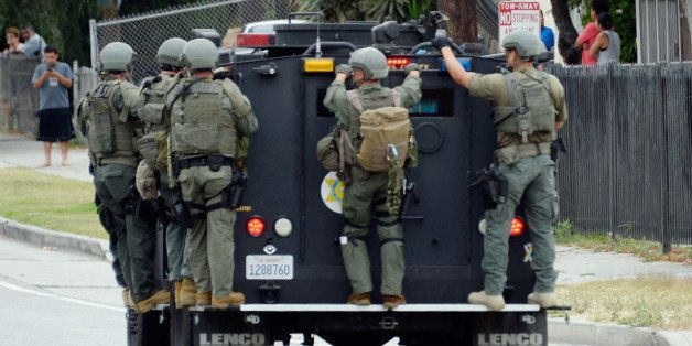 LOS ANGELES, CA - JUNE 25:  Los Angeles County Sheriff's SWAT team members standing on a armored car arrive to help Los Angel