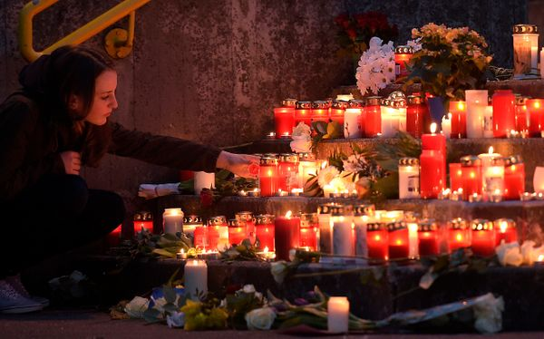 A student lights a candle in front of the Joseph-Koenig Gymnasium in Haltern, western Germany Tuesday, March 24, 2015. (AP Ph