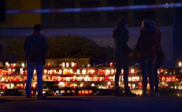 Students gather at a memorial of flowers and candles in front of the Joseph-Koenig-Gymnasium secondary school in Haltern am S