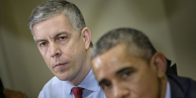 US Secretary of Education Arne Duncan (L) listens while US President Barack Obama makes a statement to the press after a meet