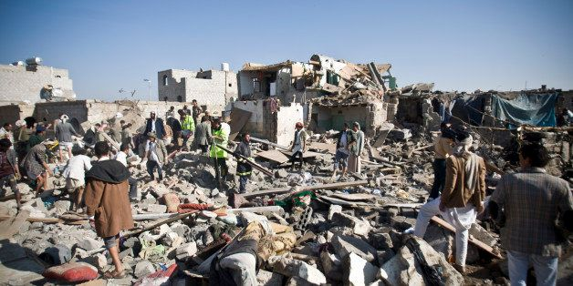 People search for survivors under the rubble of houses destroyed by Saudi airstrikes near Sanaa Airport, Yemen, Thursday, Mar