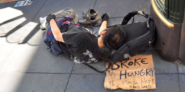 SAN FRANCISCO, CA - OCTOBER 4, 2013: A homeless man sleeps on a sidewalk in San Francisco's Union Square district. His sign d