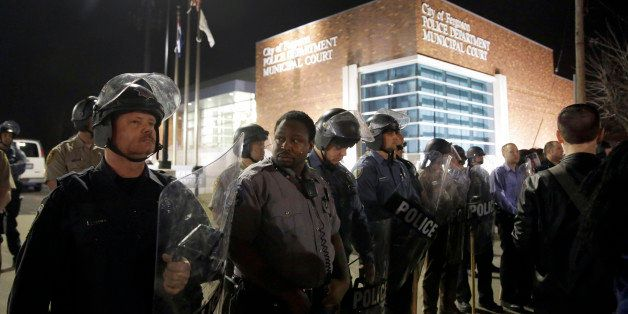 Police form a line outside the Ferguson Police Department as people demonstrate nearby Wednesday, March 11, 2015, in Ferguson
