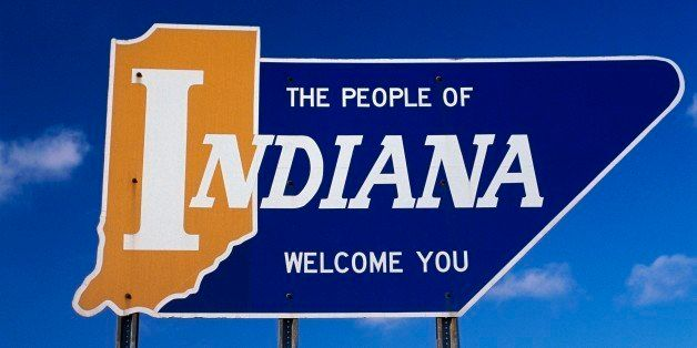 This is a road sign that says the people of Indiana welcome you. It is a welcome to Indiana road sign against a blue sky.