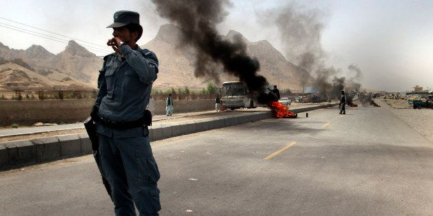 An Afghan policeman stands guard with burning tires behind as protesters block road during an anti-American protest in Kandah