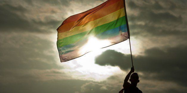 A person holds a rainbow flag during the Gay Pride Parade in San Salvador, El Salvador, on June 28, 2014. AFP PHOTO/ Jose CAB