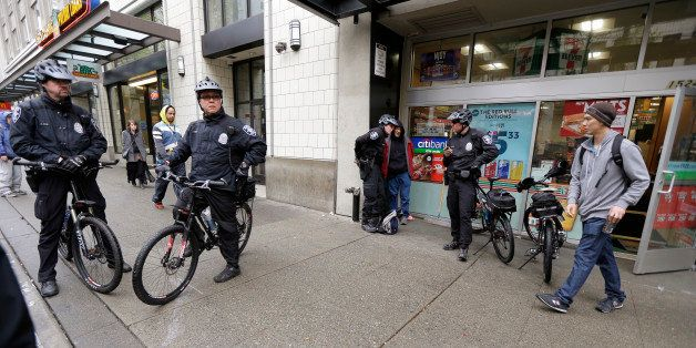 Seattle police Officers Matt Chase, left, and Tom Christenson, second from left, keep an eye on activity in downtown Seattle,