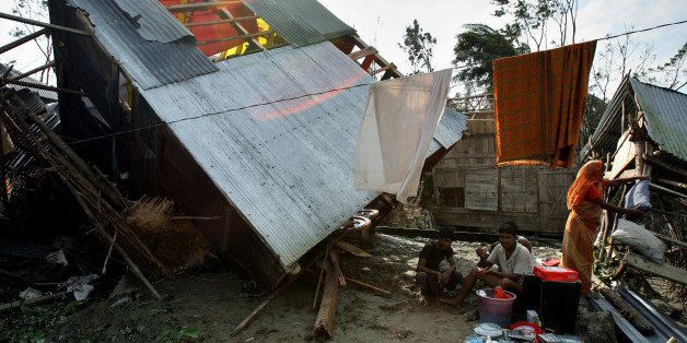 (FILES) In this picture taken on November 17, 2007, A Bangladeshi family rest next to their devastated house in Taful village