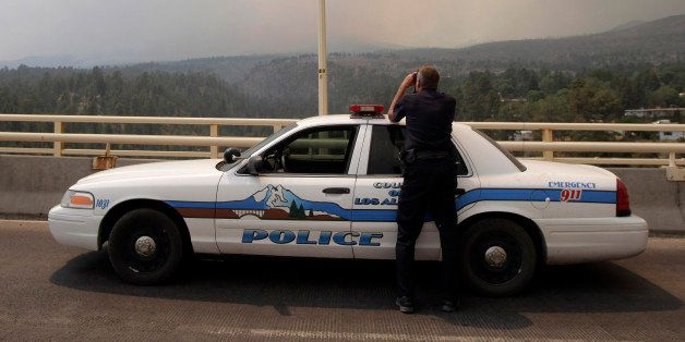 Los Alamos police officer Doug Ehler peers through binoculars to look at smoke from the Las Conchas fire in Los Alamos, N.M.,