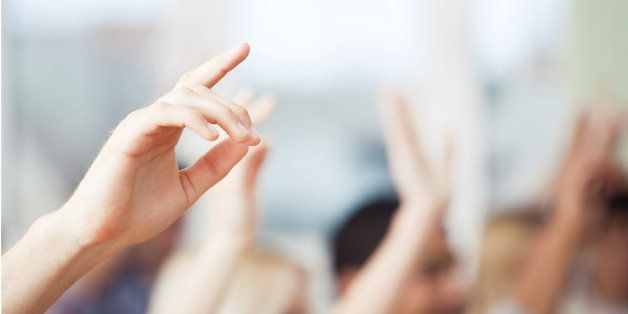 A group of students raising their hands in class.