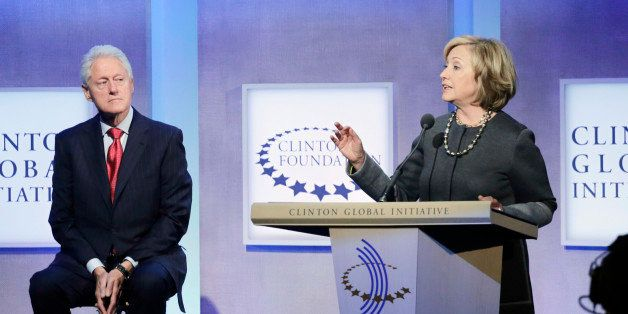 Former President Bill Clinton, left, listens to his wife, former Secretary of State Hillary Rodham Clinton, during a discussi