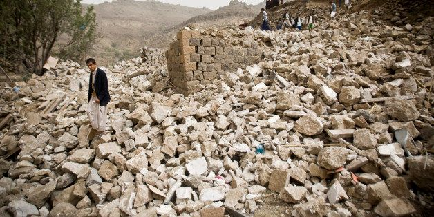 FILE -  In this Saturday, April 4, 2015 file photo, Yemenis search for survivors in the rubble of houses destroyed by Saudi-l