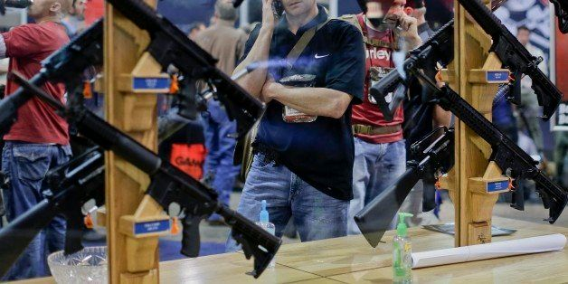A trade show attendee browses the Rock River Arms assault rifle display at the Shooting Hunting and Outdoor Trade Show, Tuesd