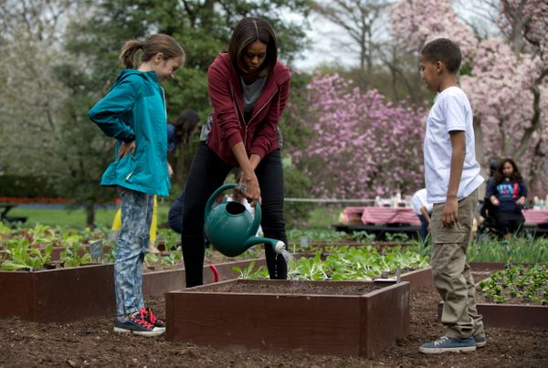 First lady Michelle Obama waters a bed of just planted vegetable seeds with students Nare Kande, 9, of the New York Botanical