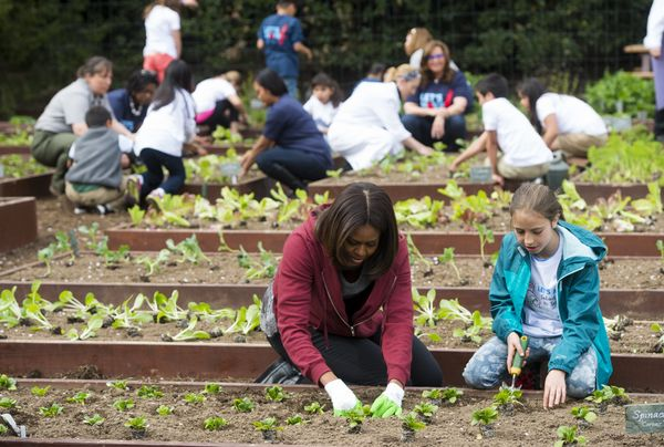 First lady Michelle Obama talks to Marley Santos, an 11-year-old from Colorado, as they plant vegetables in the White House K