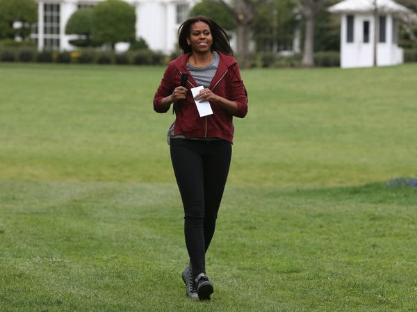 First lady Michelle Obama runs up to greet local students before planting vegetables.