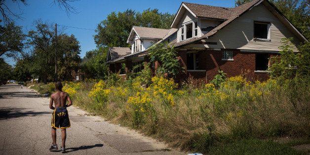 DETROIT, MI - SEPTEMBER 04:  Lawrence Payne walks past two abandoned houses on September 4, 2013 in the Six Mile Gratiot neig